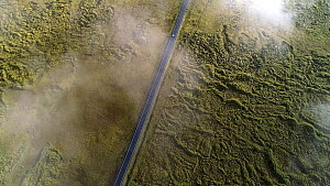 Aerial tracking shot of a car driving on Route One through the Brunahraun lava field, Iceland, August 2018. - Milan Radisics