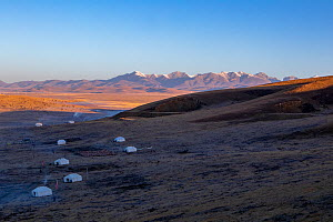 Yurts on shaded hillside, Zoige marsh and mountains in background. Ruoergai National Nature Reserve, Sichuan Province, China. October 2018. - Dong Lei