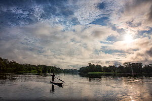 Man crossing river, with cloudy sky at sunrise, Oshwe, Democratic Republic of the Congo. May 2017.  -  Karine Aigner
