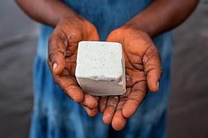 Congolese woman holding hand made palm oil soap, made by local women to sell at the market. Oshwe, Democratic Republic of Congo. May 2017.  -  Karine Aigner