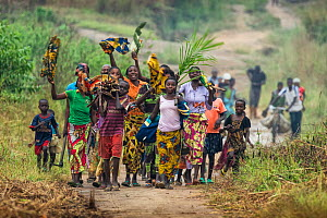 Women and children walking along road carrying fire wood and waving, Democratic Republic of Congo. May 2017.  -  Karine Aigner