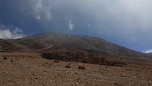 View over ice-free summit of Mount Kilimanjaro, with cloud blowing past, Tanzania, 2014.  -  Fred  Olivier