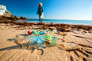 Plastic bottle litter on beach, woman gathering litter in background. March 2019.  -  Ashley Cooper