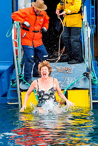 Woman taking polar plunge in 2 degrees C water off an Antarctic cruise ship into sea. Antarctic Peninsula, Antarctica. February 2019. - Ashley Cooper