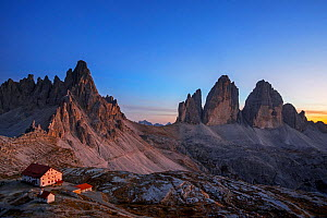 Mountain hut with Mount Paterno and three peaks of Drei Zinnen / Tre Cime di Lavaredo, in evening light. Dolomites, South Tyrol, Italy. October 2019.  -  Philippe Clement