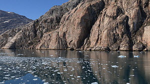 Tilt shot up from reflections to cliffs, water surface strewn with fragments of glacial ice, near Sermeq glacier, Prince Christian Sound, Greenland, 2016.  -  Fred  Olivier