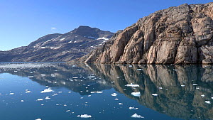 Tracking shot of reflections in calm fjord, near Sermeq Glacier, Prince Christian Sound, Greenland, 2016.  -  Fred  Olivier