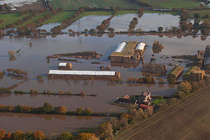 Aerial view of a flooded farm with straw bales covered with white sheeting, surrounded by fuel oil in the water, Fishlake, South Yorkshire, UK. November 2019. - David  Woodfall