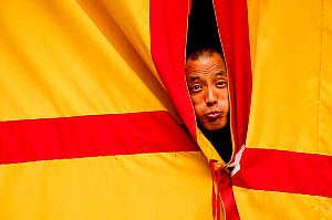 Monk peering through curtains, making a face, Hemis Buddhist Monastery, 3670 meters of altitude, Ladakh, India. September 2011.  -  Enrique Lopez-Tapia