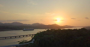 Drone shot tracking over the Panama Canal at sunset, with freighter, Panama, 2019. - Laurie Hedges