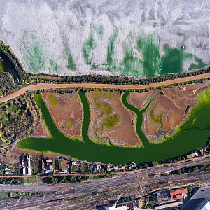 Coloured water leaking from photogypsum storage pond creates tidal channels in saltmarsh habitat. Huelva, Southern Spain. Railway lines pass nearby. Phosphogypsum is a radioactive by-product in the ma...  -  Milan Radisics