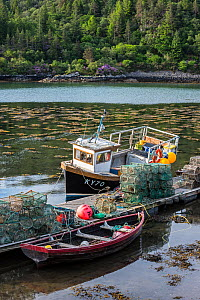 Moored small fishing boat and lobster pots / prawn creels stacked on jetty in the Plockton Harbour, Scottish Highlands, Scotland, UK  -  Philippe Clement