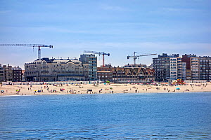 Tourists on the beach and flats and apartments being built at Nieuport / Nieuwpoort, seaside resort along the North Sea coast, West Flanders, Belgium 2019 - Philippe Clement