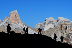 Mountain walkers silhouetted against Torre dei Scarperi / Schwabenalpenkopf, Sexten Dolomites, Parco Naturale Tre Cime, South Tyrol, Italy, October 2019  -  Philippe Clement