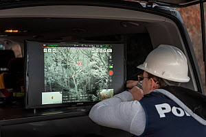 Member of the Victorian Police Remote Piloted Aircraft Systems (Police Air Wing, Specialist Response Division) looking at a screen which is displaying an infra red image, sent via a drone, of a Koala...  -  Doug Gimesy