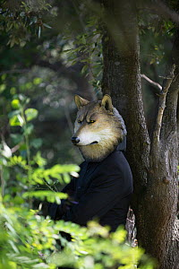 A man in a wolf mask leaning against a tree with his arms crossed, from the 'Les souffleurs, commando poétique' company, Festival 'Les Envies Rhônements' 2018. Camargue, France. - Jean E. Roche