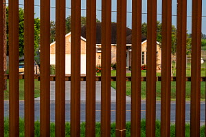 House viewed through border wall. Southmost Preserve, Nature Conservancy Reserve, Brownsville, Texas, USA. 2019.  -  Wendy Shattil