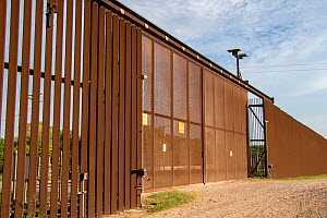 Gate along USA-Mexico border wall through Southmost Preserve. The border wall separates 85% of the reserve from the United State's side of the barrier. Nature Conservancy Reserve, Brownsville, Tex...  -  Wendy Shattil