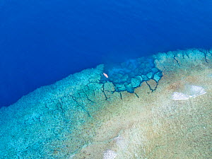 Aerial view of a dive site on the southern end of the reef surrounding the island of Yap, Micronesia. One dive boat is anchored at Yap Cavern's, a famous site for scuba divers.  -  David Fleetham