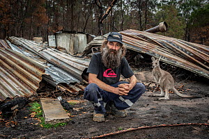 Joseph Henderson, one of the founders and managers of Wallabia Wildlife Shelter, in front of the burnt remains of his house, which was destroyed (along with the animal enclosures) during the 2019/20 b...  -  Doug Gimesy