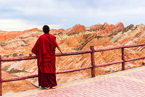 Buddhist person leaning on fence observing Rainbow Mountains. Zhangye National Geopark, China Danxia UNESCO World Heritage Site, Gansu Province, China. 2018.  -  Sylvain Cordier
