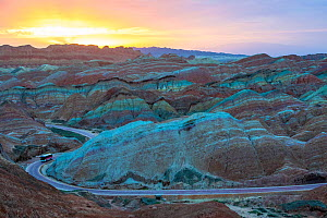 Tourist bus on winding road through Rainbow Mountains, eroded hills of sedimentary conglomerate and sandstone. At sunrise, Zhangye National Geopark, China Danxia UNESCO World Heritage Site, Gansu Prov...  -  Sylvain Cordier