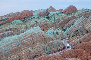 Tourist bus on winding road through eroded hills of sedimentary conglomerate and sandstone. Rainbow Mountains, Zhangye National Geopark, China Danxia UNESCO World Heritage Site, Gansu Province, China....  -  Sylvain Cordier