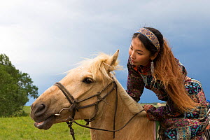 Mongol woman in traditional dress riding horse, portrait. Bashang Grassland, near Zhangjiakou, Hebei Province, Inner Mongolia, China. June 2018.  -  Sylvain Cordier