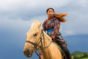 Mongol woman in traditional dress riding horse, portrait. Bashang Grassland, near Zhangjiakou, Hebei Province, Inner Mongolia, China. 2018.  -  Sylvain Cordier