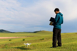 Landscape photographer operating drone in Bashang Grassland. Near Zhangjiakou, Hebei Province, Inner Mongolia, China. 2018.  -  Sylvain Cordier
