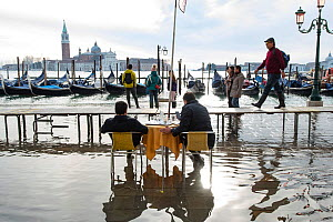 People sitting on cafe chairs looking out a flooding in Venice, Italy, December 2019.  -  Milan Radisics