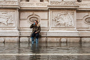 Woman in wellington boots, sitting on ledge and observing flooding in Venice, Italy, December 2019.  -  Milan Radisics