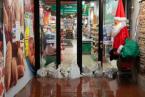 Shop with sandbags during flooding in Venice, with Father Christmas decoration, Italy, December 2019.  -  Milan Radisics
