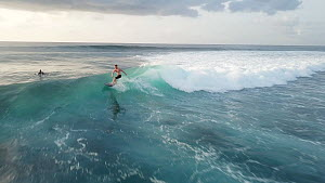 Drone shot of a surfer paddling out and surfing a wave, Maldives, 2019.  -  Laurie Hedges