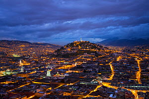View from San Juan over Quito illuminated at dusk looking twoards Panecillo Hill, Quito, Ecuador, August 2010.  -  Guy Edwardes
