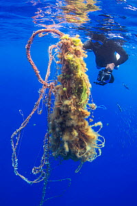Diver with floating mass of plastic pollution, Canary Islands, May.  -  Sergio Hanquet