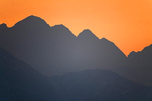 Foothills of the Tian Shan mountains, silhouetted in sunset light, Xinjiang, China  -  Staffan Widstrand / Wild Wonders of China