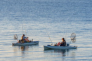 Two sea anglers fishing from pedal drive kayaks at sunset, Brittany, France, September  -  Philippe Clement