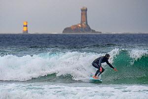 Lighthouse La Vieille and surfer in wetsuit riding a wave on surfboard at the Pointe du Raz, Finistère, Brittany, France, September 2019  -  Philippe Clement