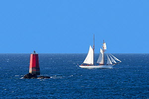 Sailing ship passing red sea mark / navigation mark on the shallows Les Vieux Moines at Pointe Saint-Mathieu, Finistere, Brittany, France, September.  -  Philippe Clement