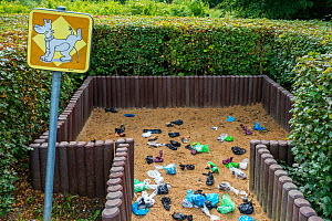 Fenced sandy public dog toilet area in city park filled with colourful discarded plastic dog poop bags, Belgium  -  Philippe Clement
