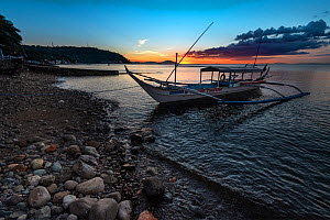 Bangka boat at sunset, a double outrigger dive boat, with coastal scenery, Balayan Bay, Batangas, the Philippines. Minimum fees apply.  -  Magnus Lundgren