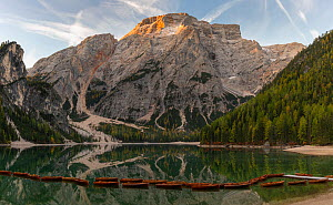 Rental rowboats tied together and first light on Croda del Becco mountain. Lago di Braies, Dolomites, Italy, October 2019.  -  John Shaw