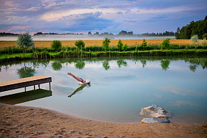 Girl diving into a pond on a foggy evening, Tartumaa county, Southern Estonia. Model released  -  Sven Zacek