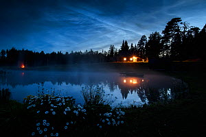 Noctilucent or night shining clouds in sky on a midsummer night, above a pond / lake with cabin and bonfire along the edge. Valgamaa county, Southern Estonia. June 2019.  -  Sven Zacek