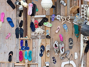 Plastic rubbish, mainly shoes, washed ashore and used to decorate wall, Wizard Island, Cosmoledo Atoll, Seychelles  -  David Tipling