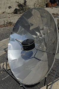Solar cooker, with a reflective parabolic dish focusing heat from the sun onto a metal casserole pot, within a renewable energy display at ITER Bioclimatic village, near El Medano, Tenerife, August.  -  Nick Upton
