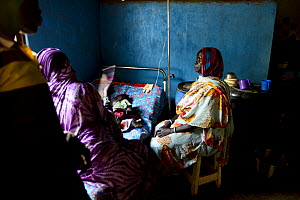 Girl rests while being treated for malaria in the small rural hospital in Moukoulou, southern Chad. Her family watches over her. Malaria disease is very common in this part of the country in the rainy...  -  Enrique Lopez-Tapia