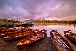 Rowing boats and jetties along the shore of Derwentwater, morning light and rainbow, Keswick, Cumbria, The Lake District, UK. October 2019.  -  Ross Hoddinott