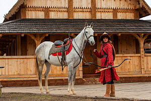 Cossack woman standing with Akhal-Teke horse in front of wooden building at Kievan Rus Park, a reconstruction of the former capital Rus. Ukraine, 2020.  -  Kristel Richard